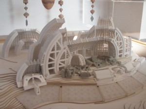 The model shows a completed Arcosanti, but only the gray buildings in the foreground are built at this point.