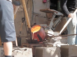 Molten bronze is poured into sand molds